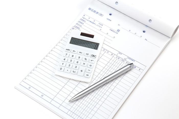 見積もり用紙の上に置かれた電卓とペン