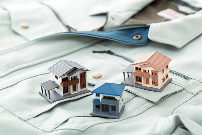 作業着の上に置かれた家の模型