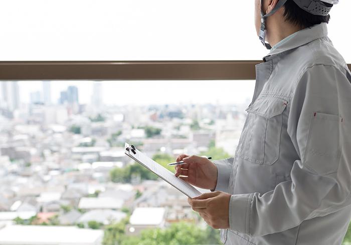 街並みを眺める作業着の男性