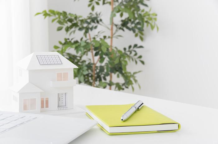 白い机に置かれた筆記用具と家の模型