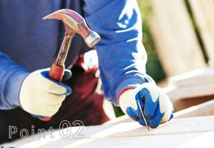 手袋をつけて釘を打つ男性